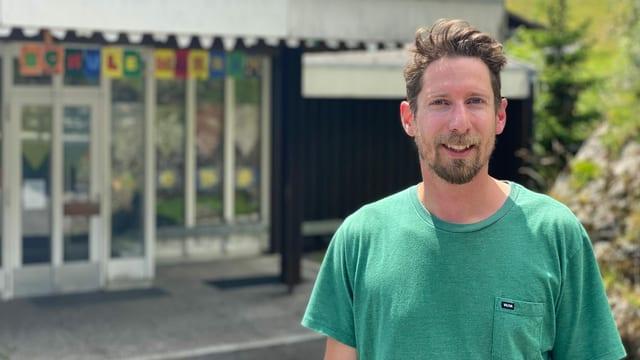Mann steht vor Schulhaus