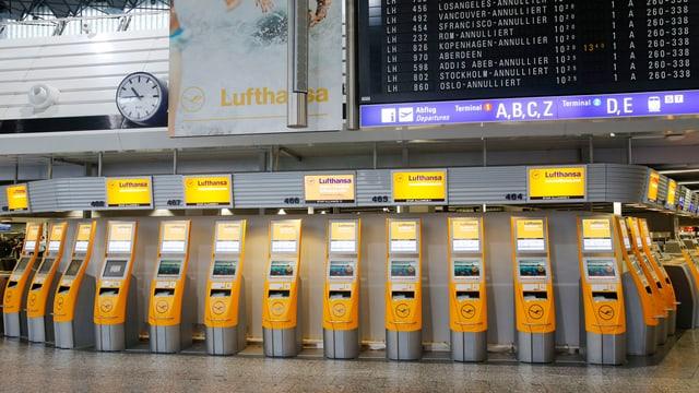 Leere Check-In-Schalter, Anzeigetafel mit annullierten Flügen.