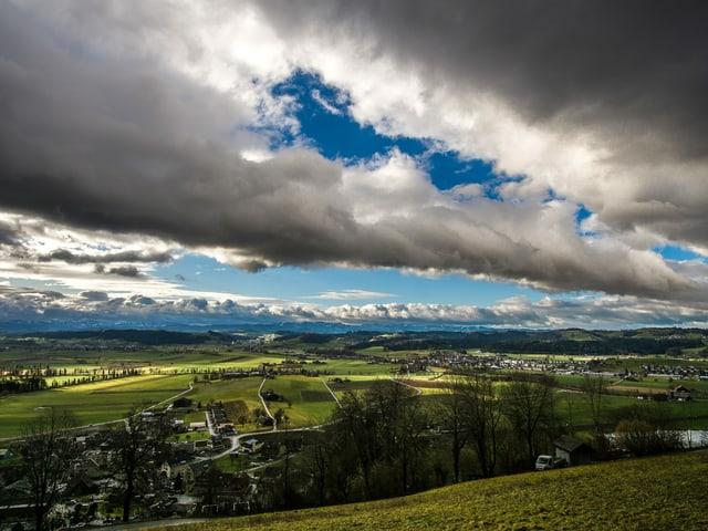 Bewölkter Himmel, dazwischen zeigt sich etwas Blau über dem grünen Mittelland