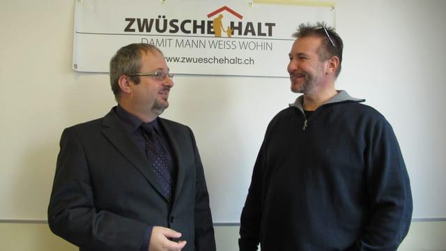 Hunziker und Müller stehen vor dem Schild mit dem Logo und dem Aufdruck «Zwüschehalt»