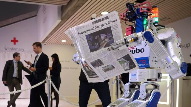 Ein Roboter mit Zeitung am WEF.