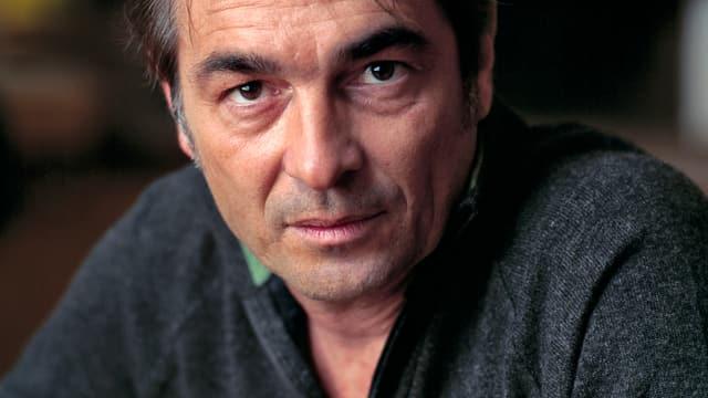 Porträtfoto von Stefan Gubser im grauen Wollpullover