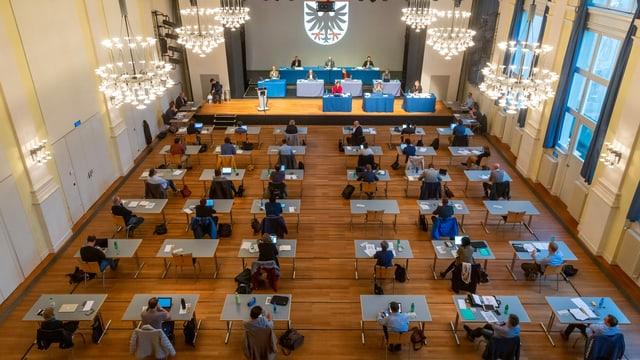 Ratssitzung in einem grossen Saal, alle Personen an eigenem Tisch.