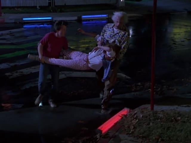 Nachts auf einer Strasse. Im Randstein sind blaue und rote Leuchten eingelassen.
