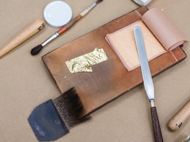 Spachtel und Pinsel neben einem Holzbrett auf dem eine Goldfolie liegt.