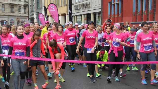 Läuferinnen in pinkfarbenen Shirts und schwarzen Leggins warten auf den Startschuss.