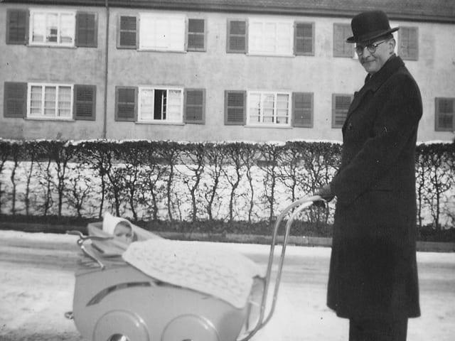 Ein Mann mit Hut und langem Mantel vor stösst einen Kinderwagen, in dem ein Baby mit einer Mütze sitzt.