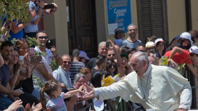 Der Papst und ein kleines Mädchen reichen sich die Hände.