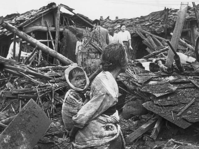 Eine Grossmutter mit ihrem Kind in einem zerstörten Teil von Pjöngjang.