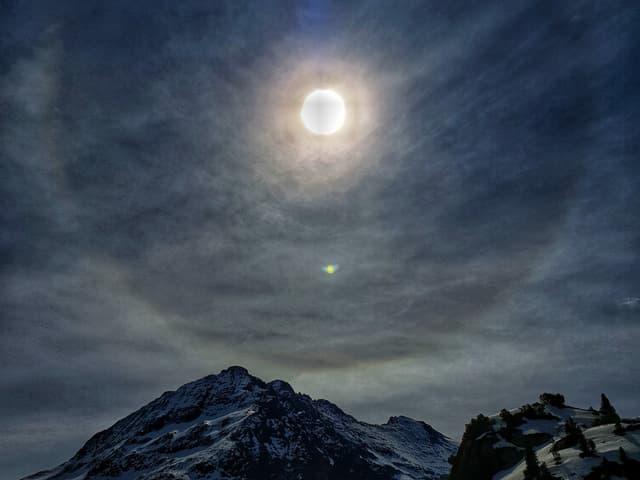 Milchiger Himmel mit Kreis um die Sonne, der in allen Regenbogenfarben leuchtet.