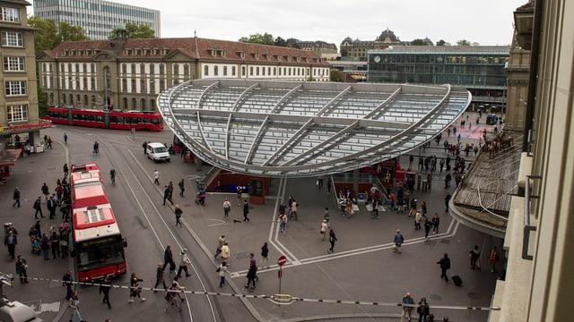 Der Bahnhofsplatz in Bern mit Bussen, Leuten und dem Baldachin.