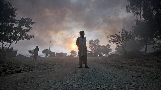 Zwei Männer stehen auf einer Strasse in der Provinz Khyber-Pakhtunkhwa. Dicke Rauschwaden bedecken den Himmel nach einem Angriff im Oktober 2010. (reuters)
