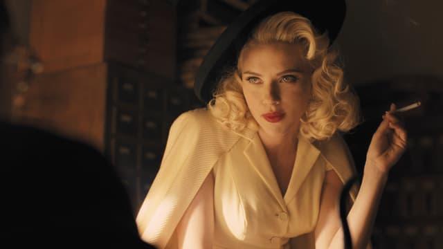 Scarlett Johansson im Stil von Marilyn Monroe mit blonden Locken, Hut und Zigarette.