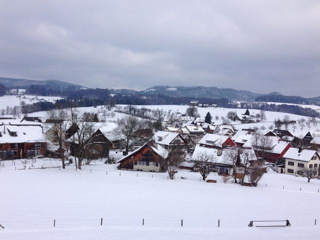 Blick auf das verschneite Rifferswil von einem Hügel aus