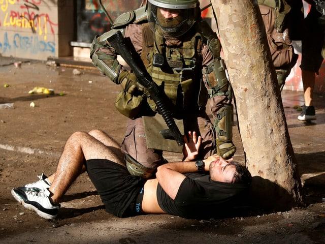 Polizist richtet Waffe auf Demonstranten am Boden