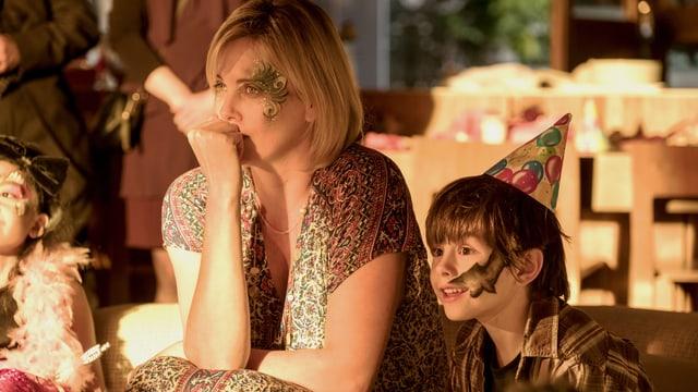 Eine Mutter sitzt neben ihrem Sohn an einer Party