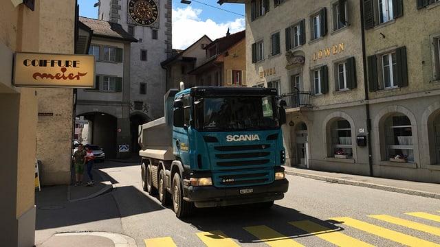 Ein Lastwagen fährt durch eine Innenstadt.