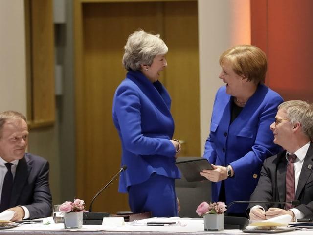Angela Merkel und Theresa May lachen zusammen.