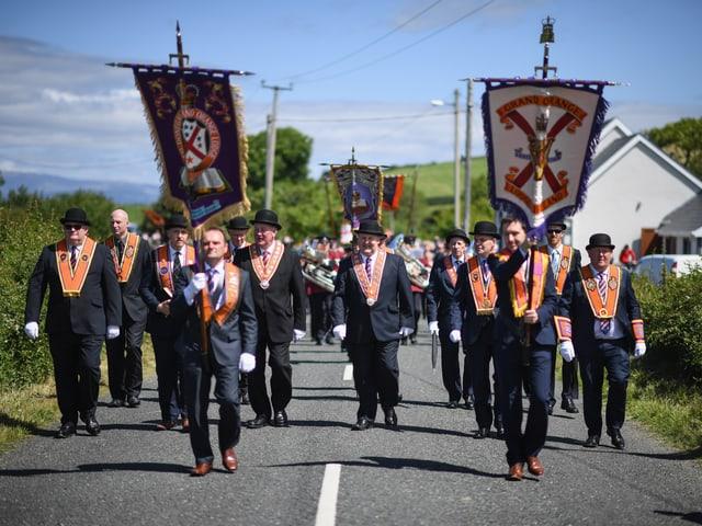 Eine grosse Gruppe von Mändern in schwarzen Anzügen mit Orangen Bannern um den Hals läuft in einem Umzug eine Überlandstrasse entlang.