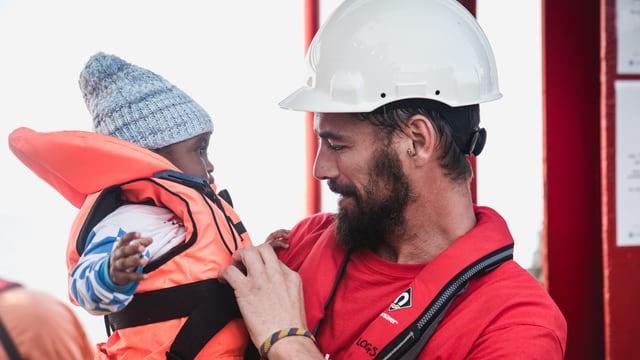 Ein gerettetes Kind und ein Helfer auf dem Rettungsschiff Vos Hestia.