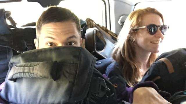 Moderator Pät sitzt neben Kamerafrau Ilona hinten in einem Auto. Auf Pät ist das Gepäck bis zur Nase gestapelt.