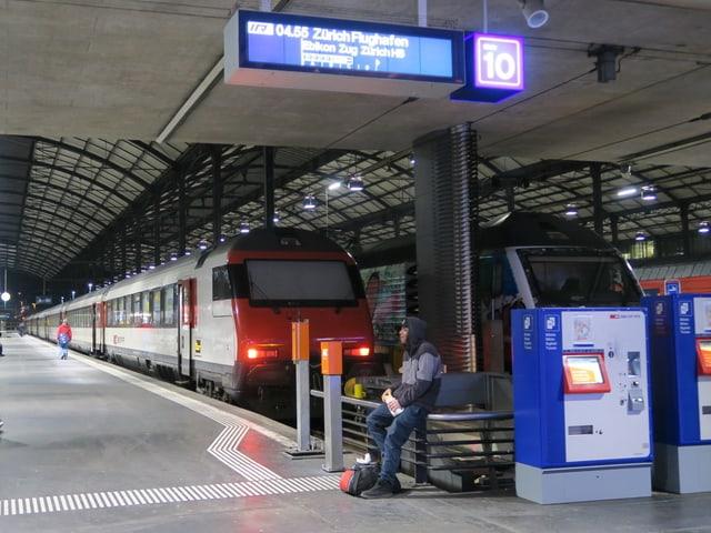 Ein fast leeres Perron mit der Anzeigetafel und der wartende Zug.