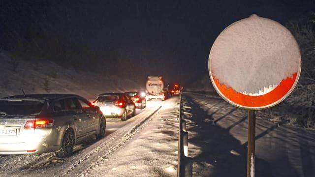 Verschneite Autobahn mit Kolonne.