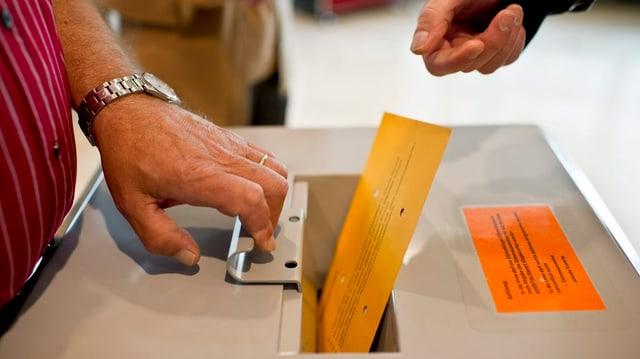 Zwei Personen an der Wahlurne.