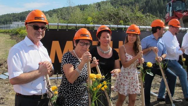 Fontana und seine Familie mit orangen Helmen auf dem Kopf und blumengeschückten Spaten in den Händen.
