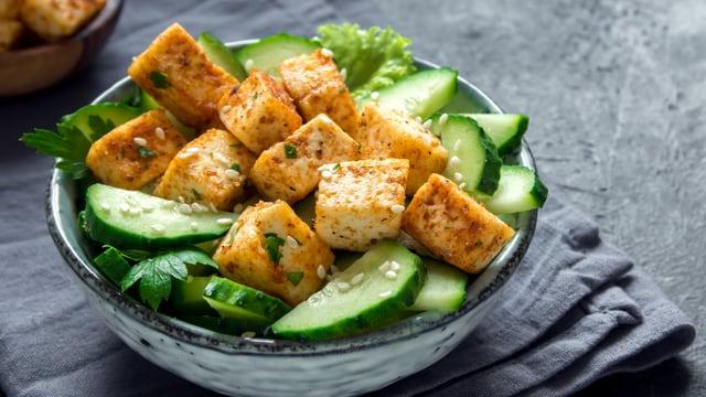Ein Teller mit Tofu und Gurken