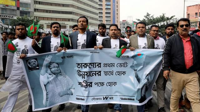 Bangladeschi mit einem Wahlplakat für die amtierende Premierministerin