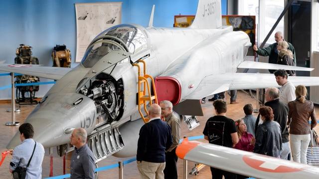 Besucher im Militärflugzeugmuseum Payerne betrachten einen ausgemusterten Tiger F5 Kampfjet