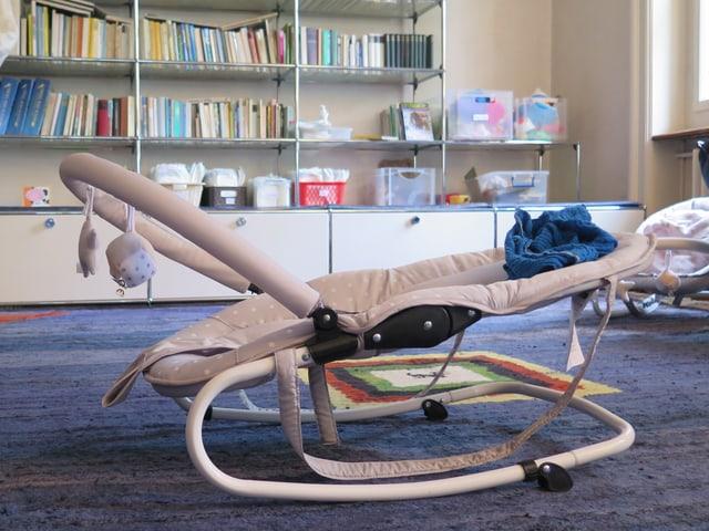 Blick ins Wohnzimmer, mit UMS-Möbel, Bücher und Wiege.