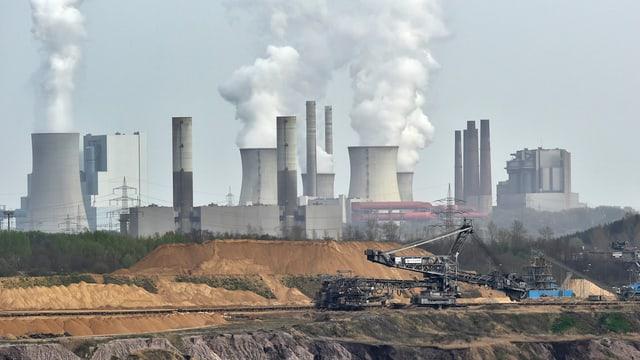 Im Vordergrund wird Kohle abgebaut, im Hintergrund steht ein grosses Kraftwerk.