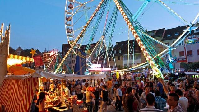 Ein Jahrmarkt mit Ständen und einem leuchtenden Riesenrad, überall hat es Menschen.