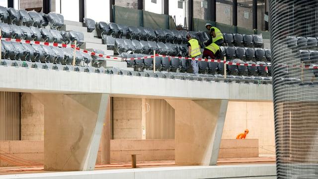 Bauarbeiter montieren Stühle für die künftige Zuschauertribüne.