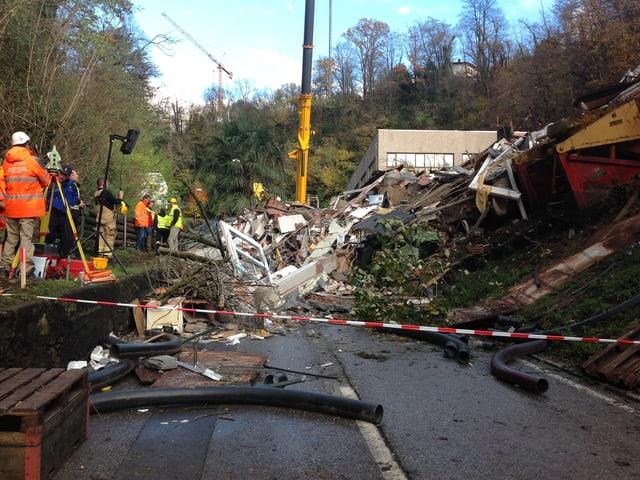 Ein Erdhaufen mit Trümmern auf einer Strasse hinter einer Absperrung