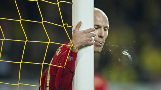 Arjen Robben vom FC Bayern München hält sich nach einem verschossenen Elfmeter kurz vor Spielschluss am Torpfosten fest und spuckt aufs Feld.
