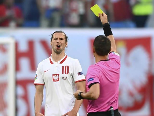 Der Schiedsrichter zeigt die gelbe Karte.