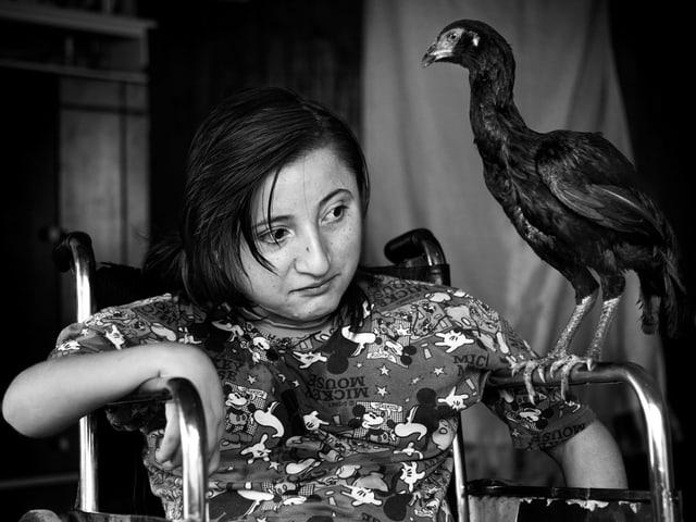 Ein Mädchen im Rollstuhl, auf dessen linker Armlehne ein schwarzer Vogel sitzt.