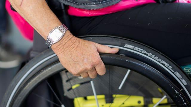 Frauenhand an Rollstuhlrad