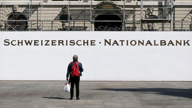 Ein Mann mit rotem Ruckstack steht vor dem Nationalbank-Gebäude.