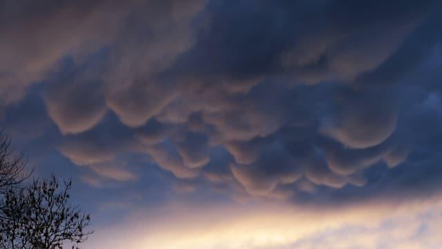 Dunkler Himmel mit Violettschattierungen mit Wolkenbäuchen, die nach unten hängen.