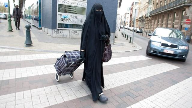 Eine verschleierte Frau überquert eine Strasse