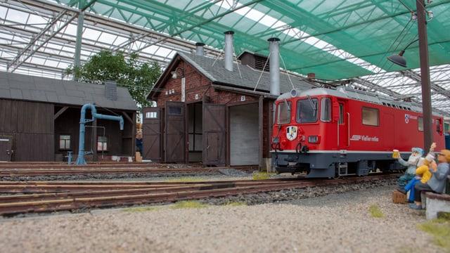 Gartenbahn, roter Zug mit Modellfiguren am Gleis