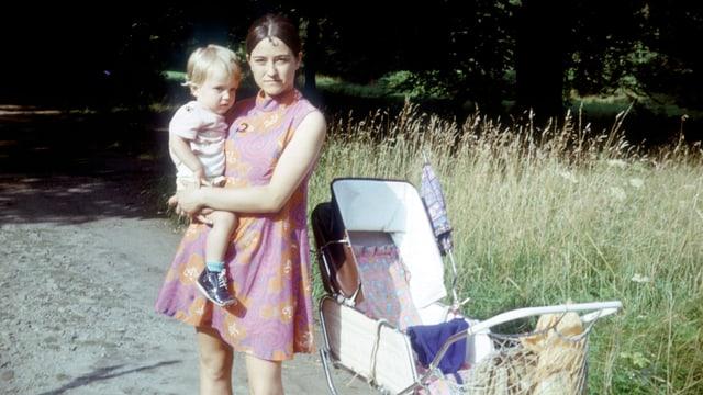 AUf einer alten Aufnahme hält eine junge Mutter ein Kind im Arm.