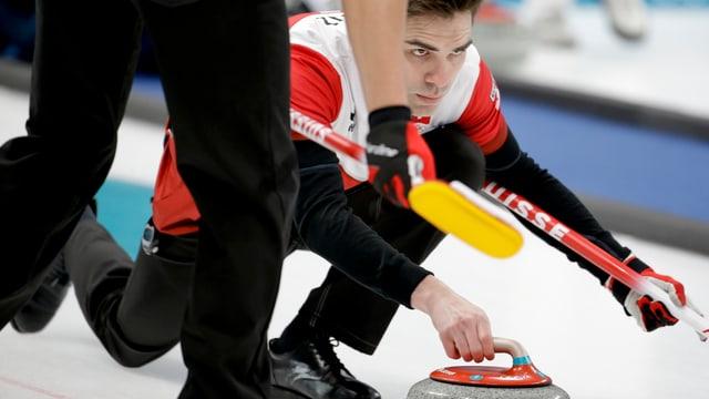Purtret da Peter De Cruz che sajetta in dals craps da curling.