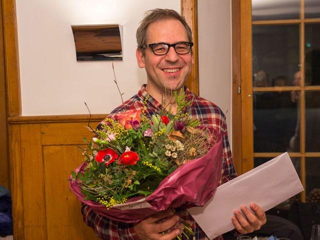 Ein Mann blickt lachend in die Kamera, in der Hand einen Blumenstrauss und zwei Couverts.