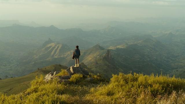 Ein Junge steht auf einer Erhöhung und schaut auf eine weitreichende, grüne Berg- und Tallandschaft.