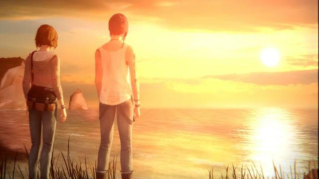 Zwei Mädchen stehen auf einer Klippe am Meer.